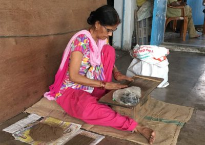 Women roll the incense sticks by hand